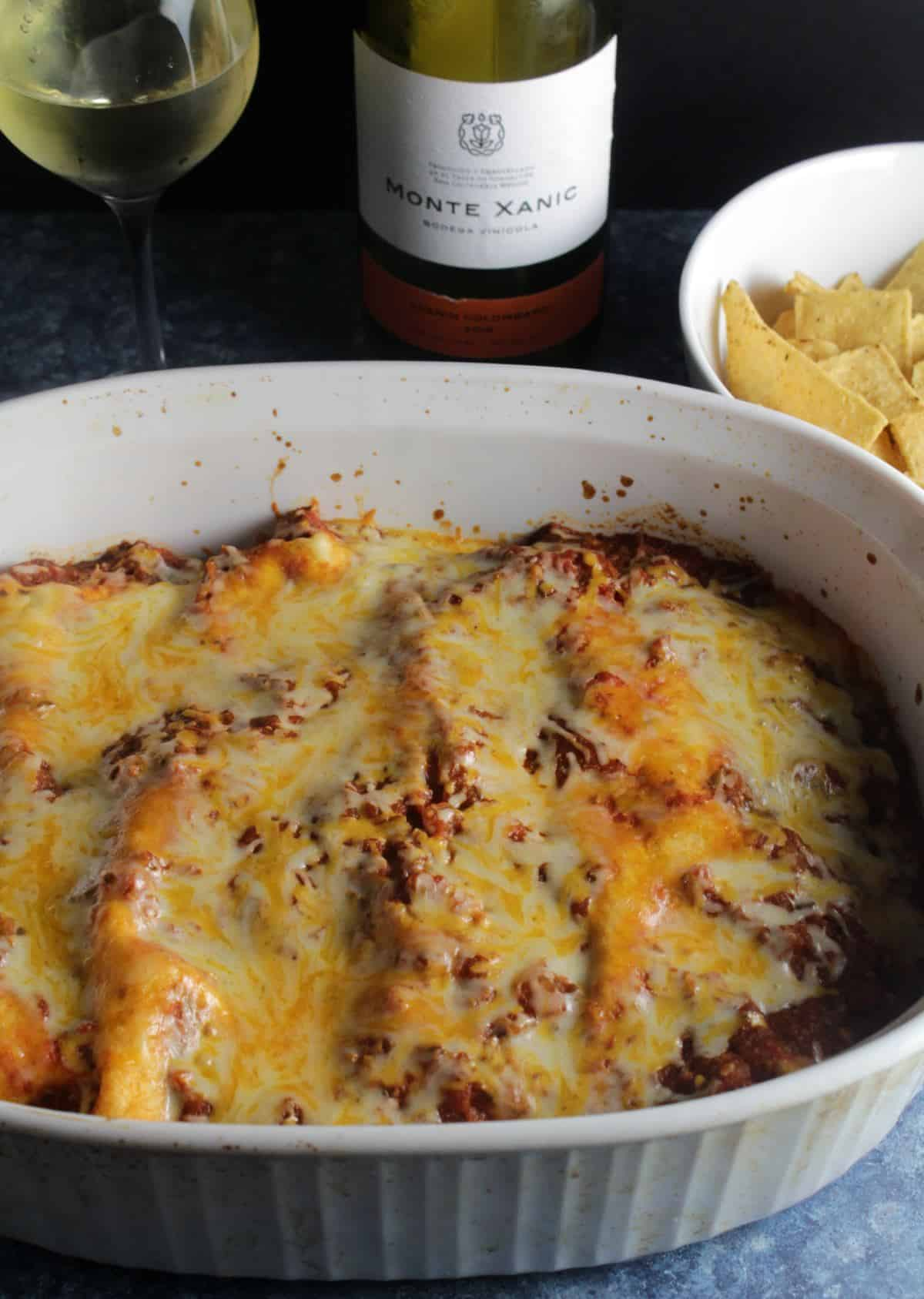enchiladas in a baking dish served with a white wine.