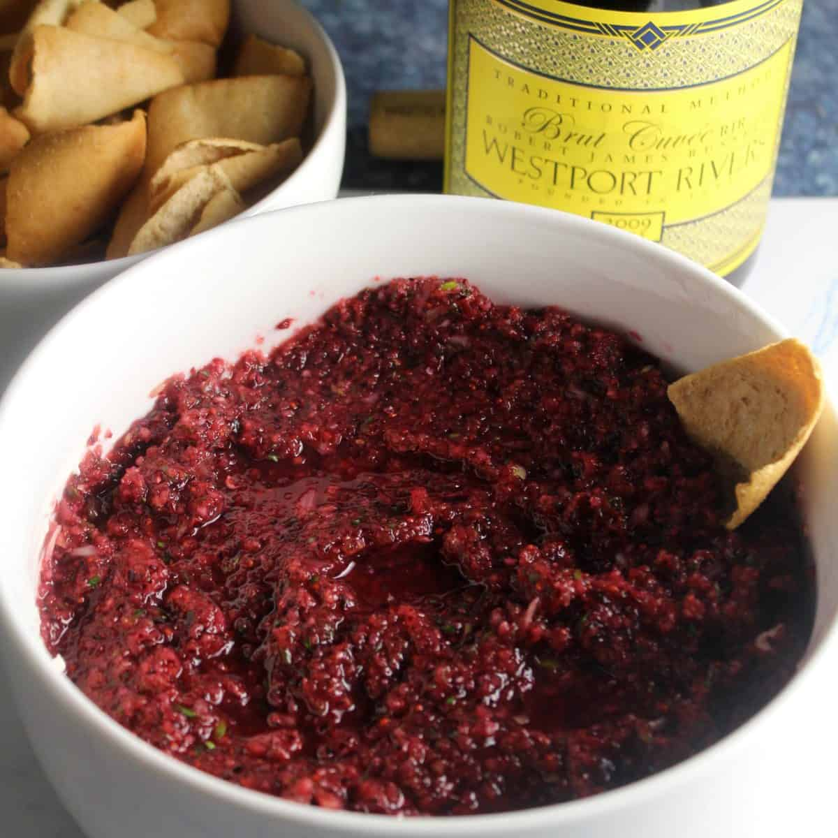 white bowl with cranberry dip served with a bottle of Westport Rivers Brut Cuvée.