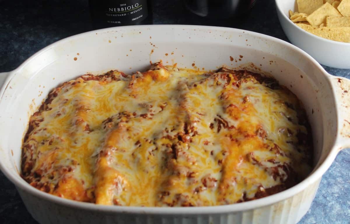 ground turkey enchiladas in a white baking dish, topped with melted cheese.