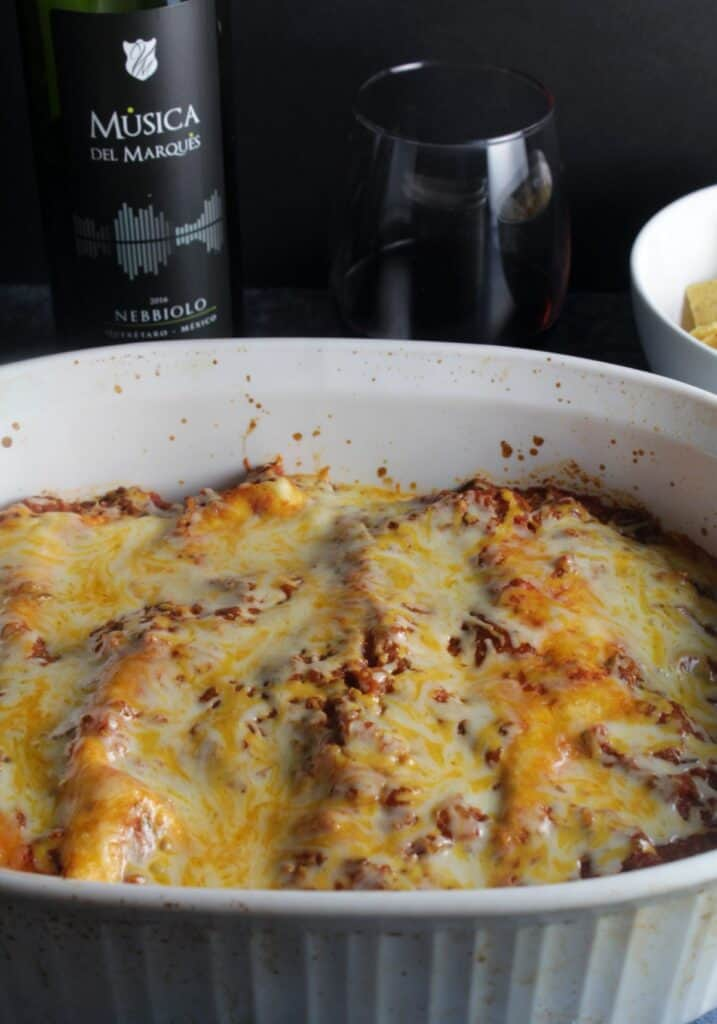 turkey enchiladas in a baking dish with red wine in the background