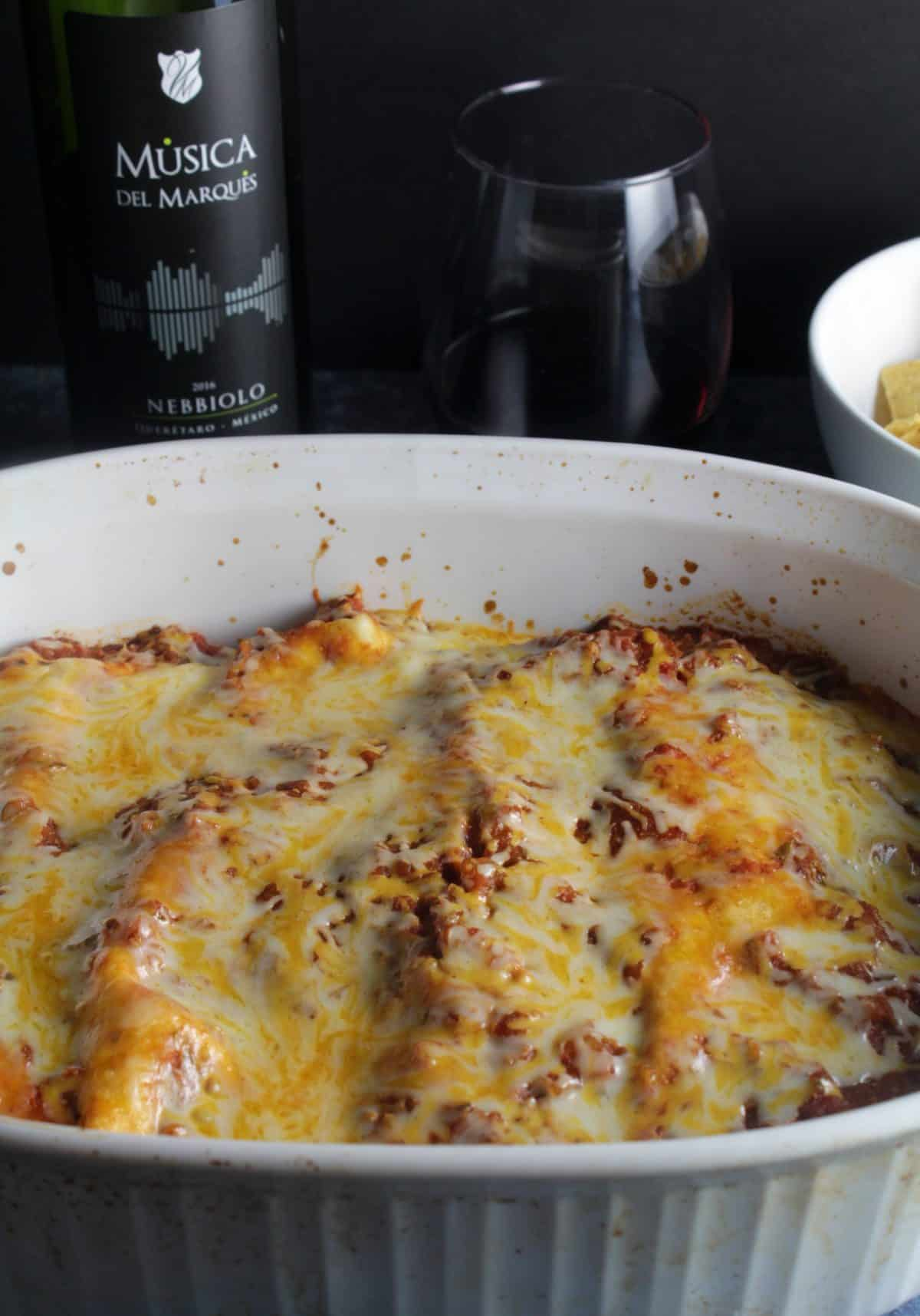 Ground Turkey Enchiladas in a baking dish, topped with cheese and sauce, and served with a red wine.