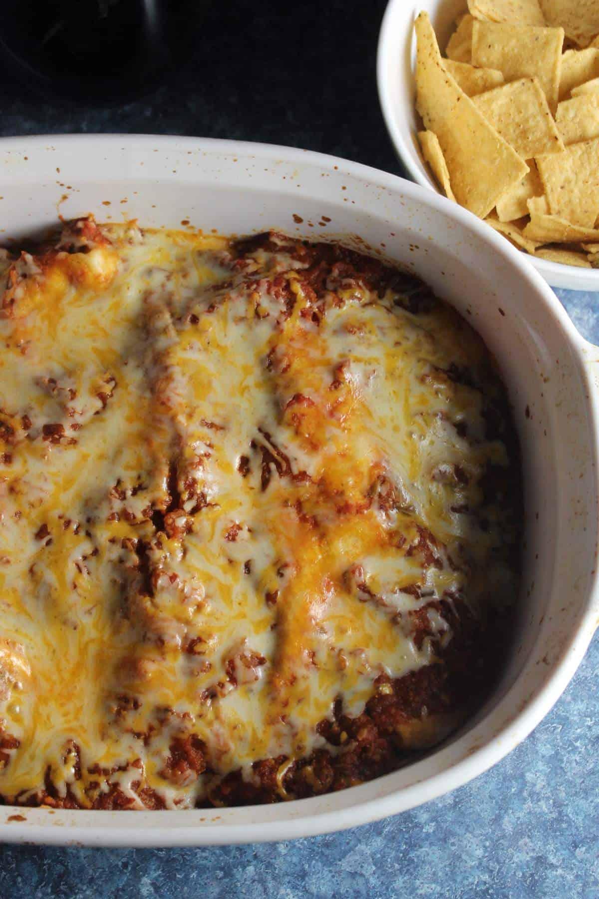 Ground turkey enchiladas in a baking dish, served with tortilla chips.