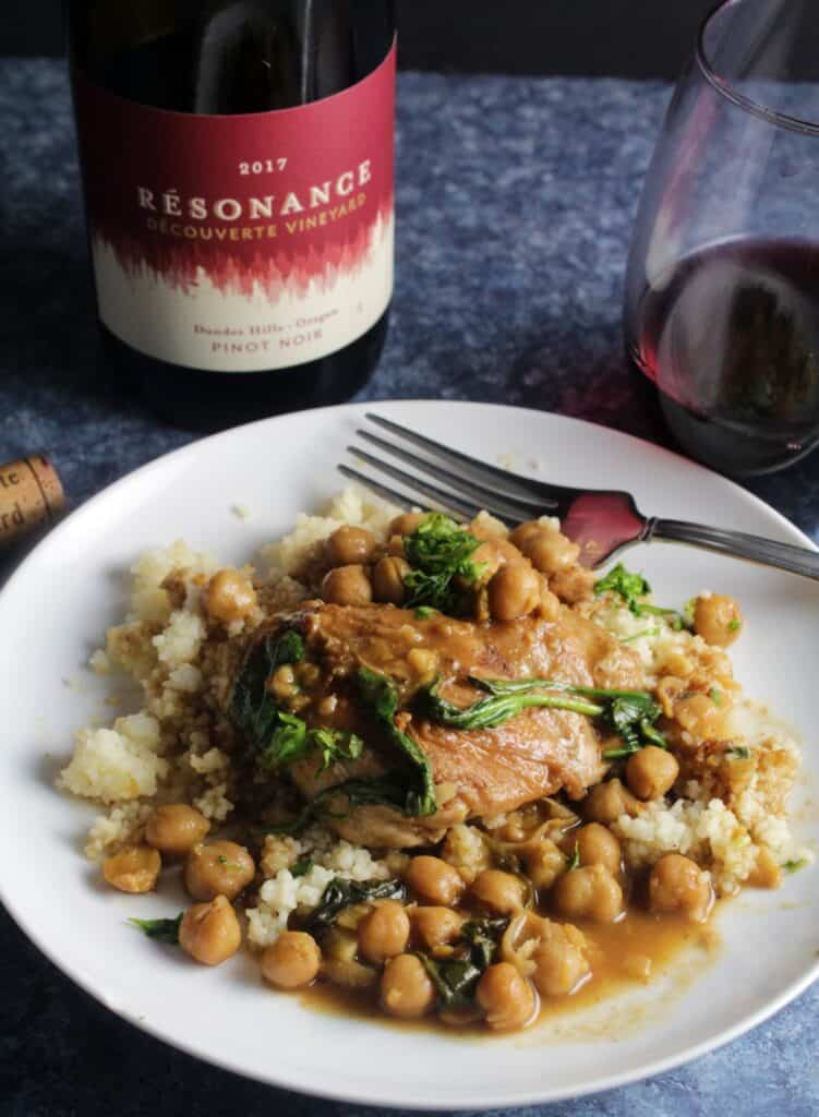 braised Moroccan chicken with chickpeas, served over couscous on a white plate. Bottle of Pinot Noir in the background.
