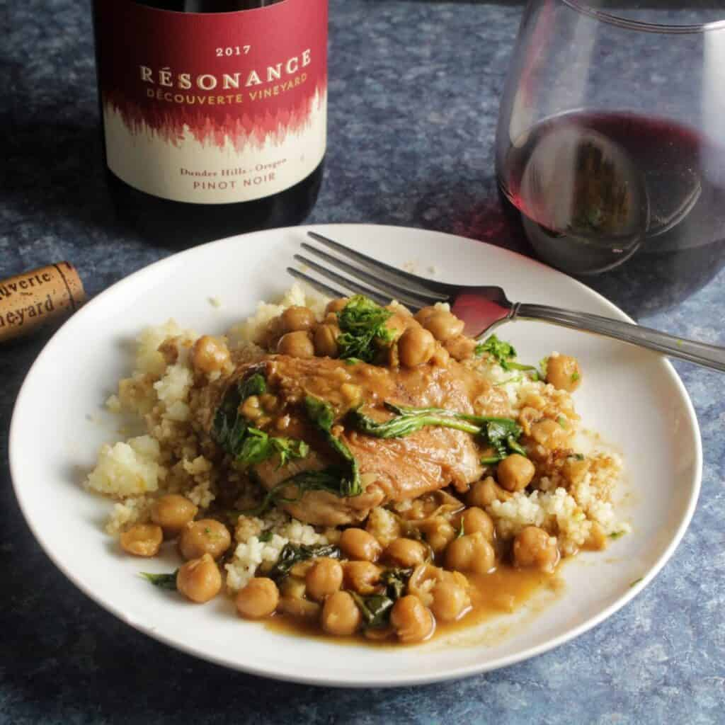 braised Moroccan chicken thighs with chickpeas, served over couscous with a bottle and glass of Pinot Noir red wine in the background.