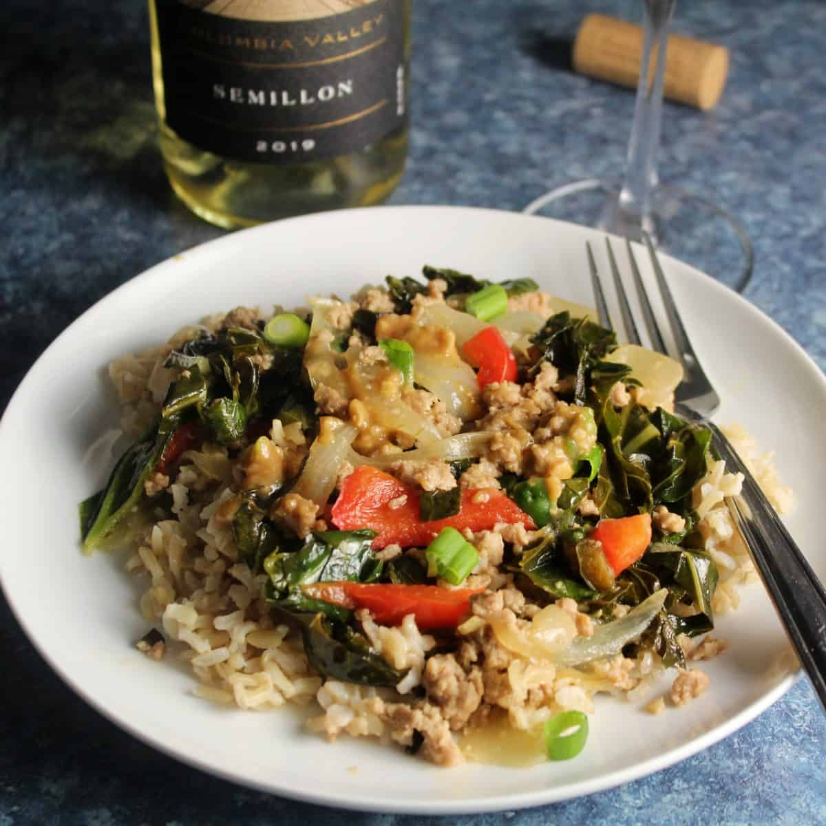 ground pork stir fry with collard greens, served over rice, on a white plate. Bottle of wine in the background.