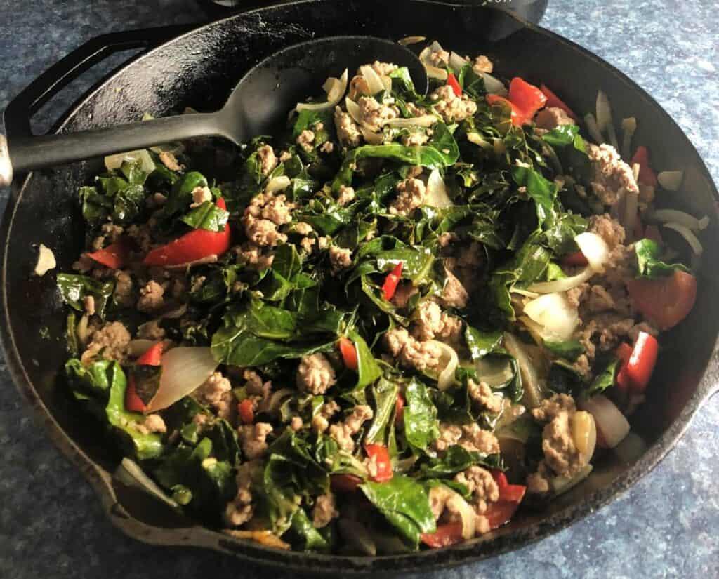 stirring ground pork stir fry with collard greens in a black skillet.