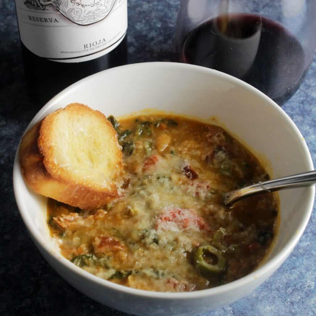 bowl of white bean soup with sausage, garlic bread and a glass of Rioja wine.