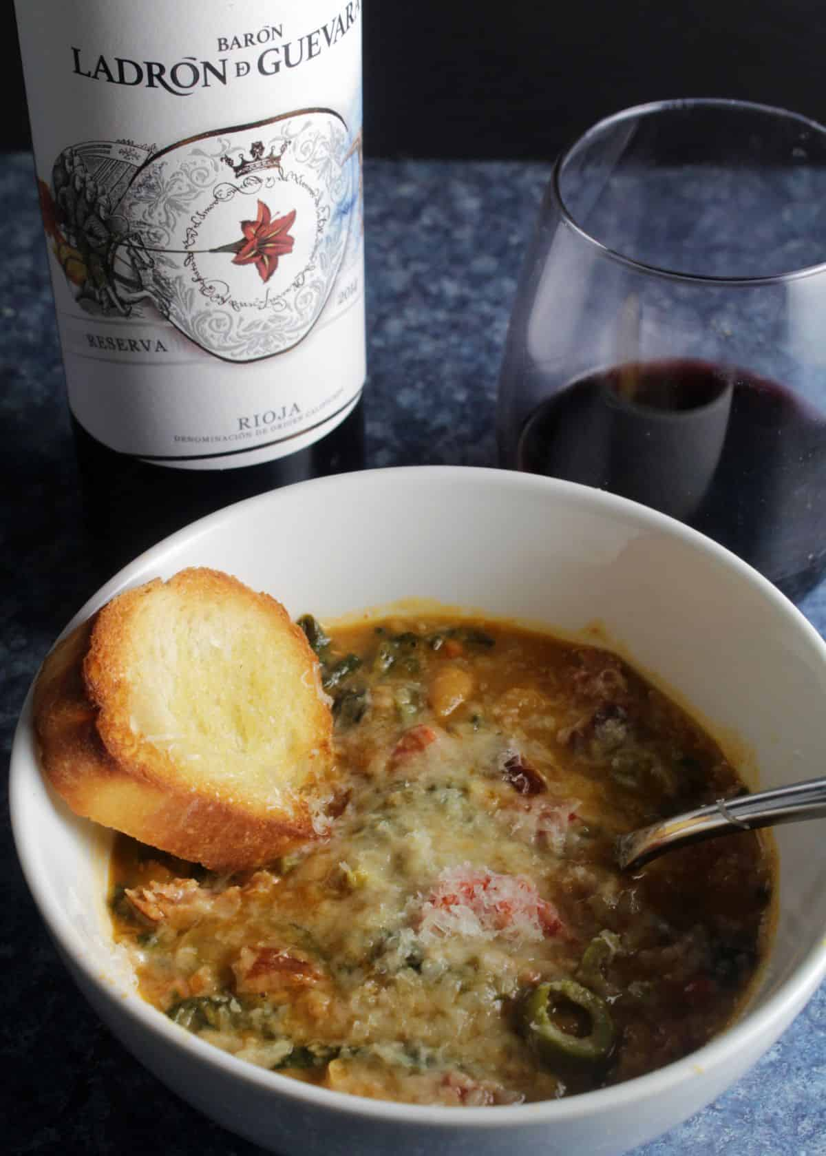 white bean stew in a white bowl served with garlic bread and a glass of Rioja wine.