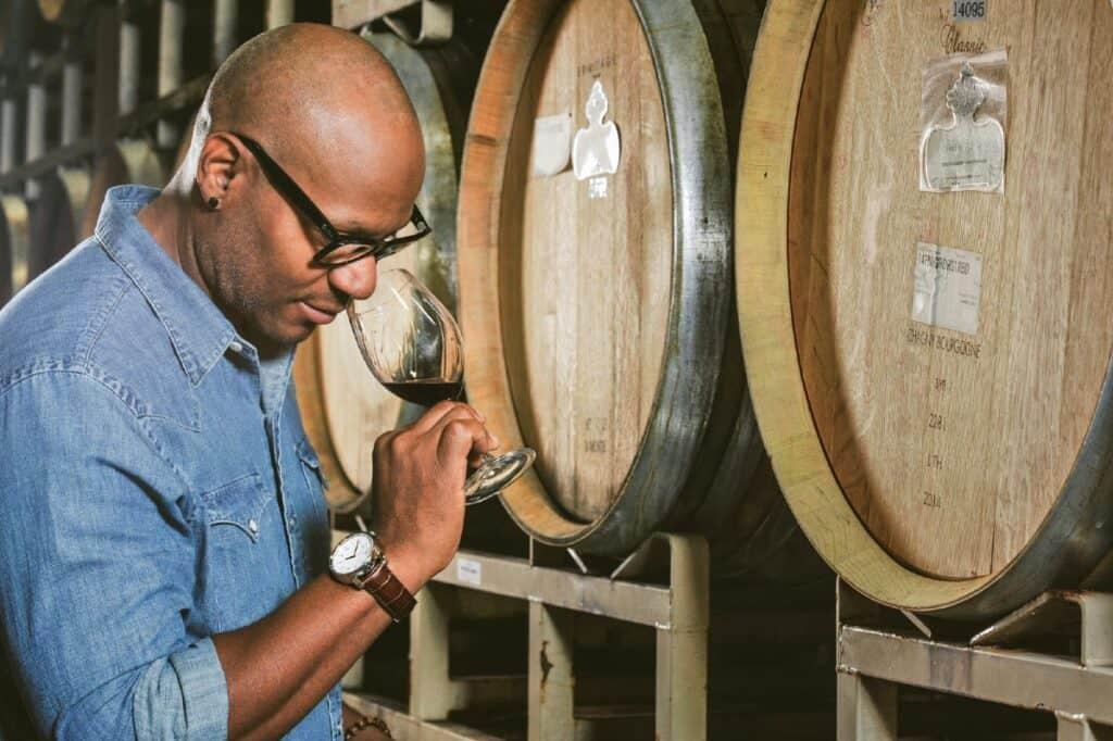 André Hueston Mack tasting wine with wine barrels behind him.