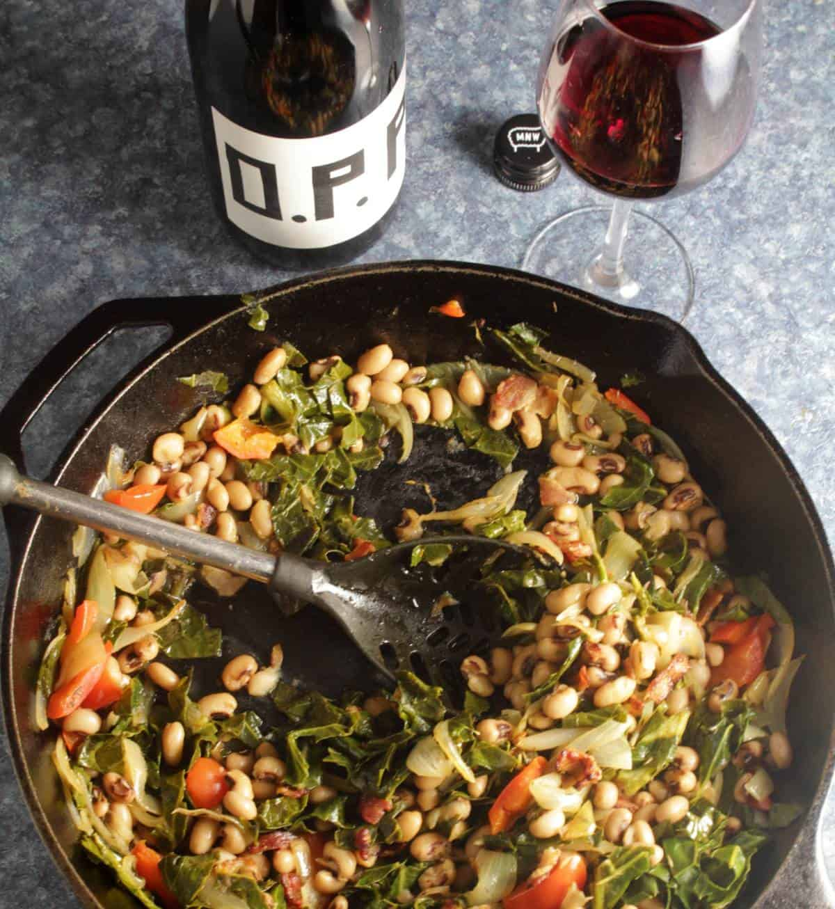 skillet with black-eyed peas and collard greens, served with a red wine.