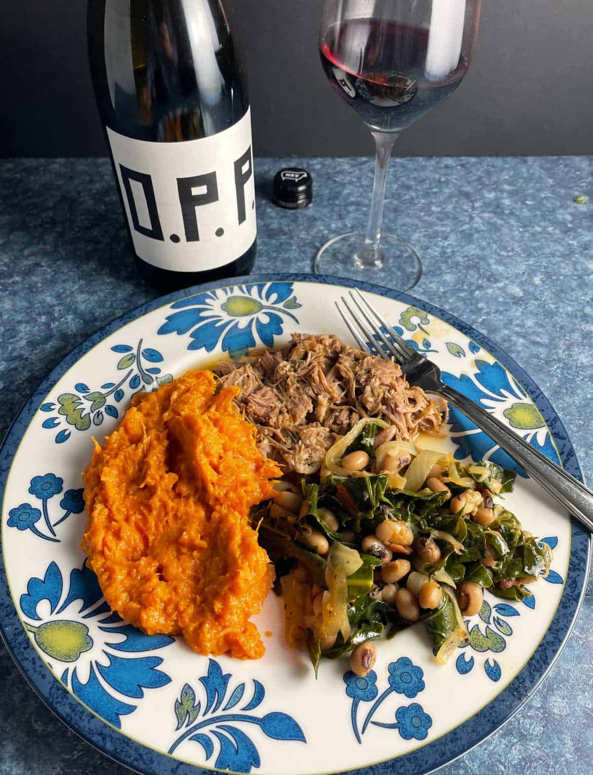 black-eyed peas with collard greens on a plate with pulled pork and sweet potatoes. Served with a red wine.