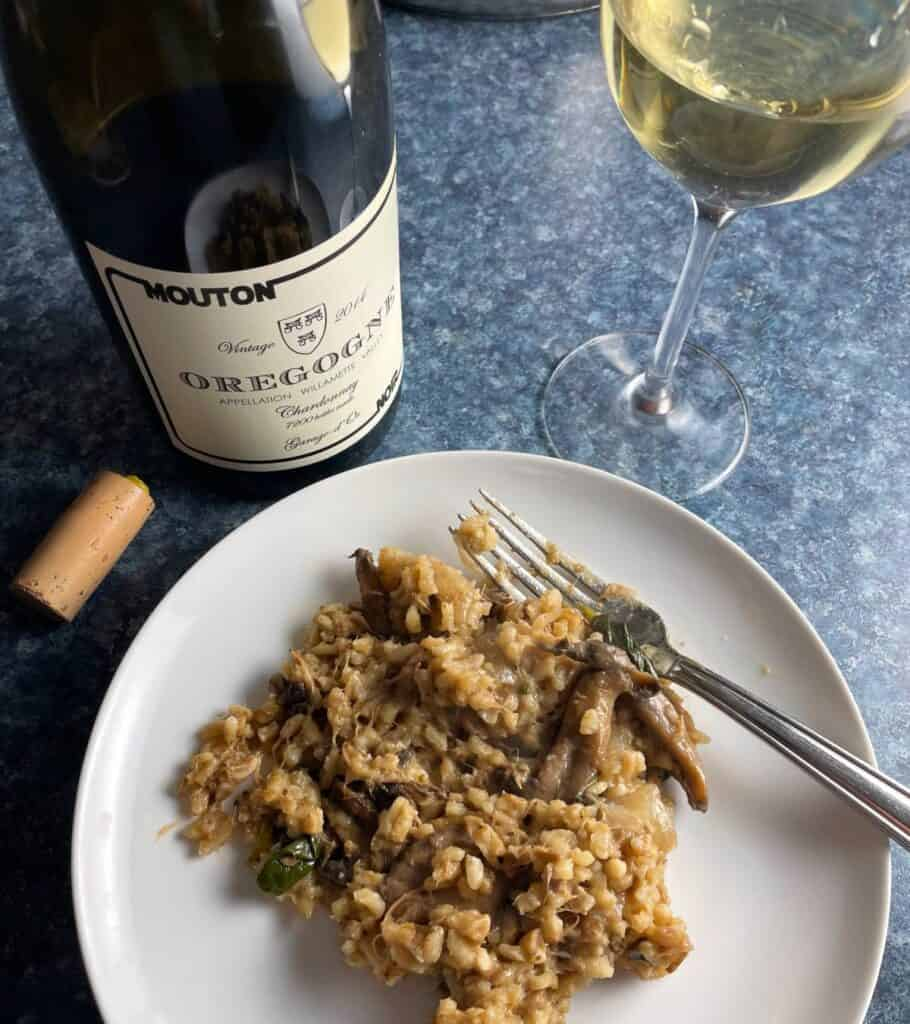 pulled pork risotto on a white plate, served with Oregogne Chardonnay.