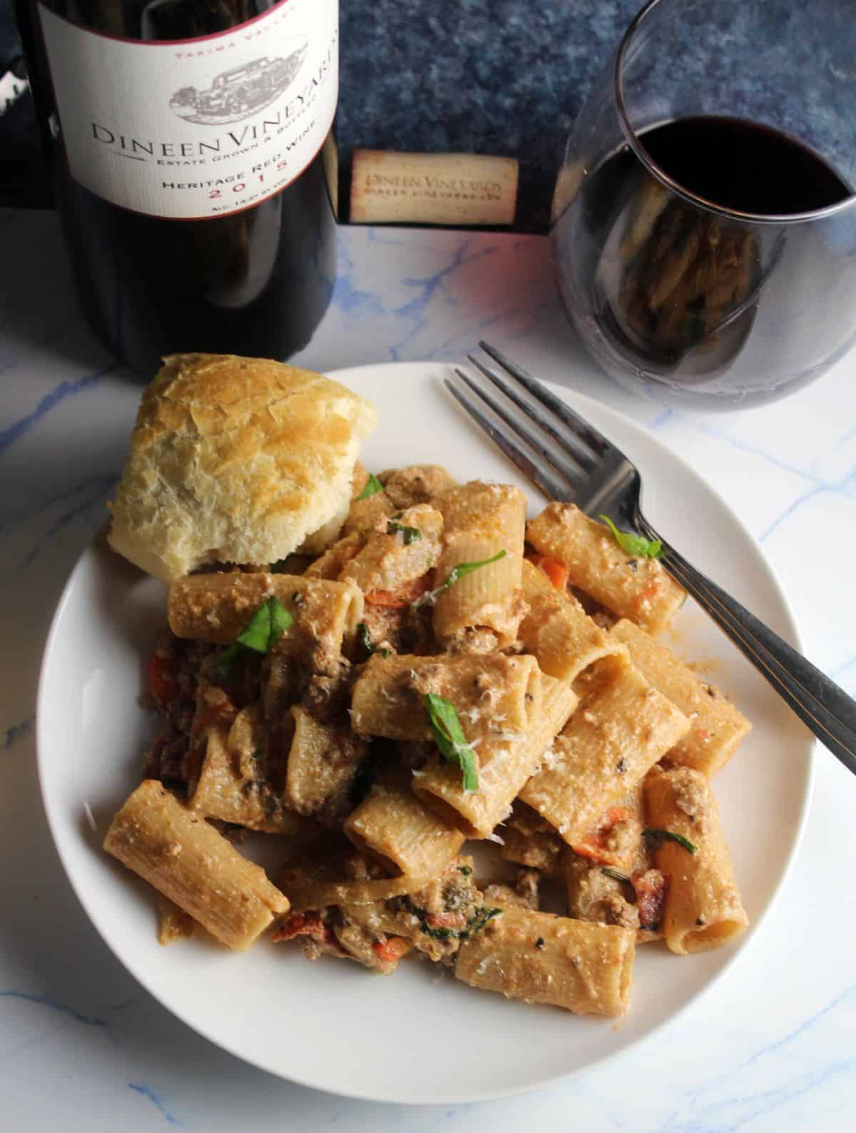 lamb ragu rigatoni on a white plate served with red wine.