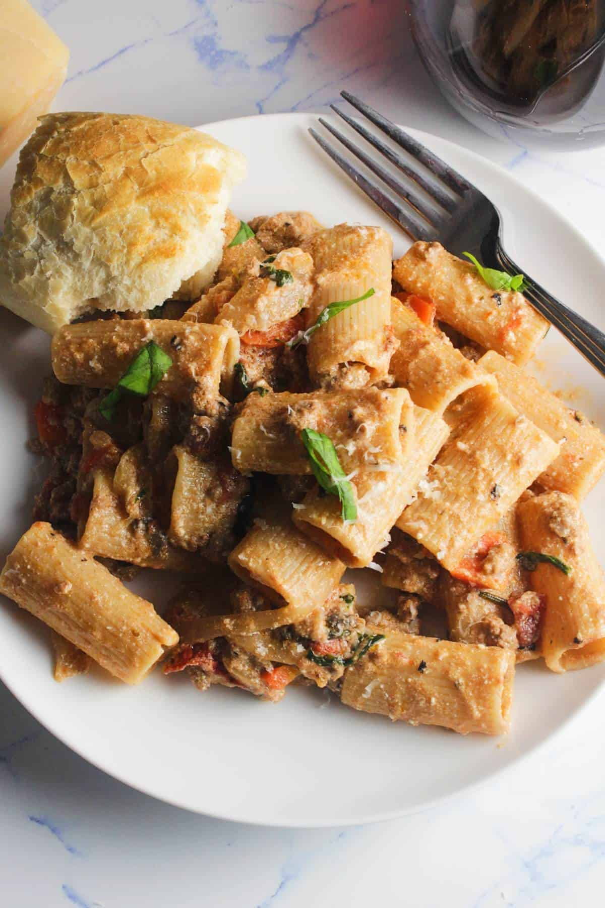 rigatoni tossed with lamb ragu sauce, served on a white. plate.