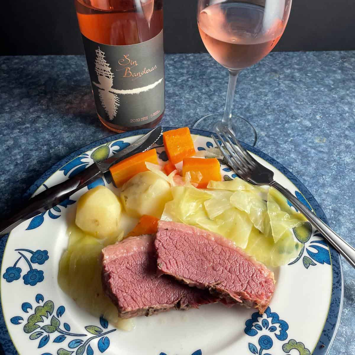corned beef and cabbage on white plate with blue flowers on the edge, paired with a rosé wine.