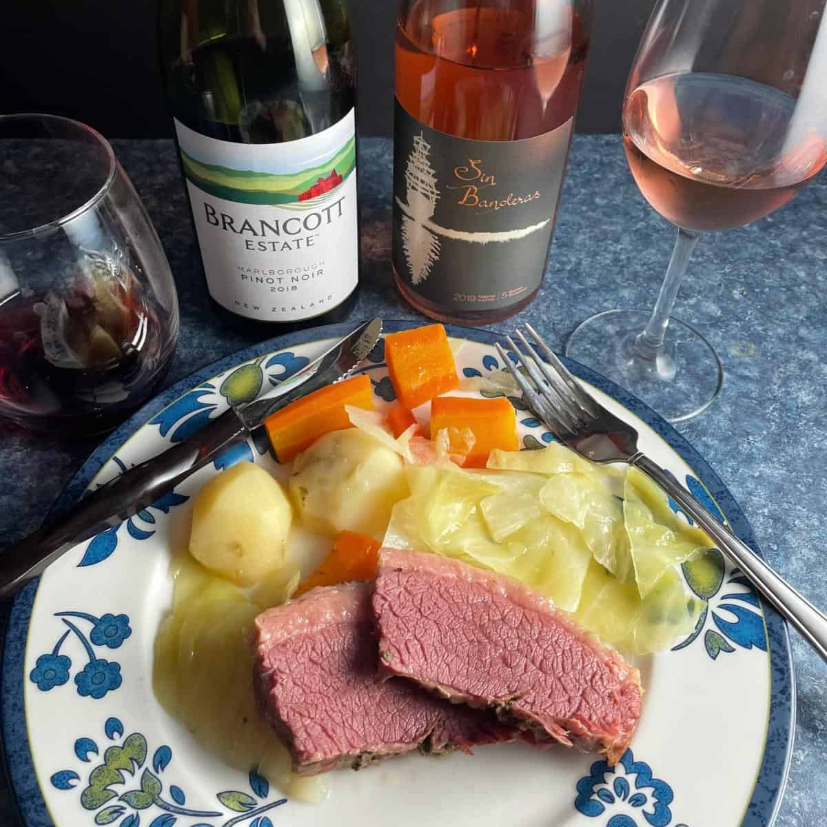 plate of corned beef and cabbage served with a rosé wine and a Pinot Noir.