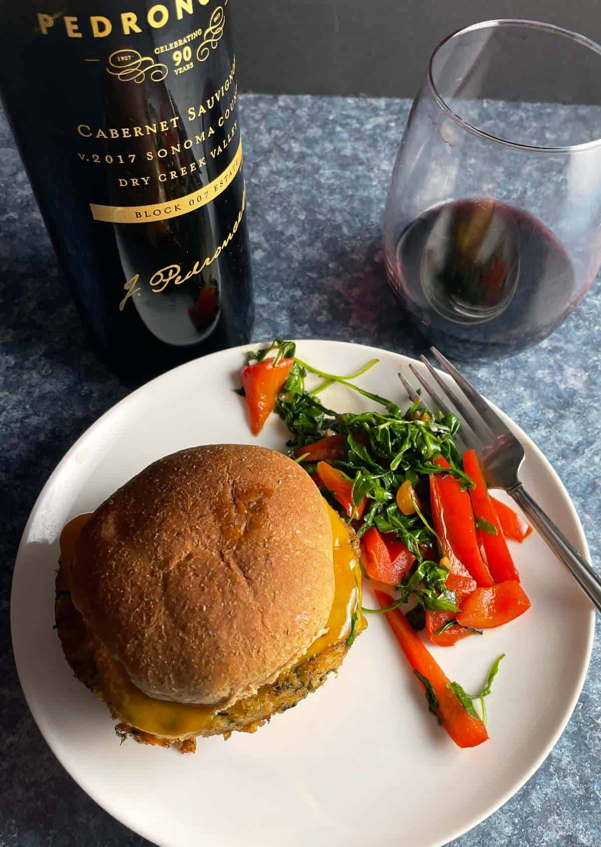 cooked arugula and red peppers on a white plate with a burger, served with a red wine.