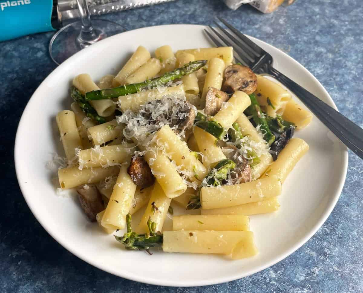 roasted asparagus and mushrooms tossed with ziti and served on a white plate, topped with grated cheese.