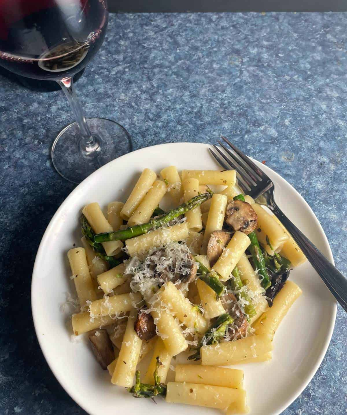 asparagus and mushroom ziti served on a white plate with a glass of red wine.