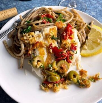 pan seared sea bass topped with a sauce including olives, red peppers and parsley. Served with pasta and a slice of lemon.