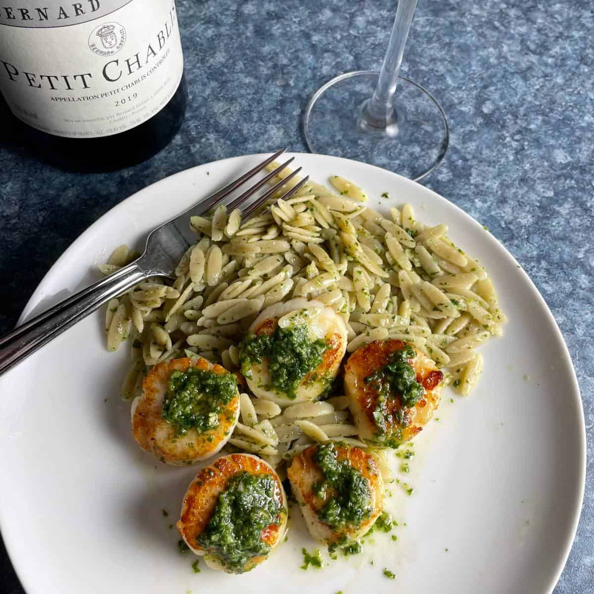 scallops topped with pesto, plated with orzo, and served with a bottle of Chablis wine.