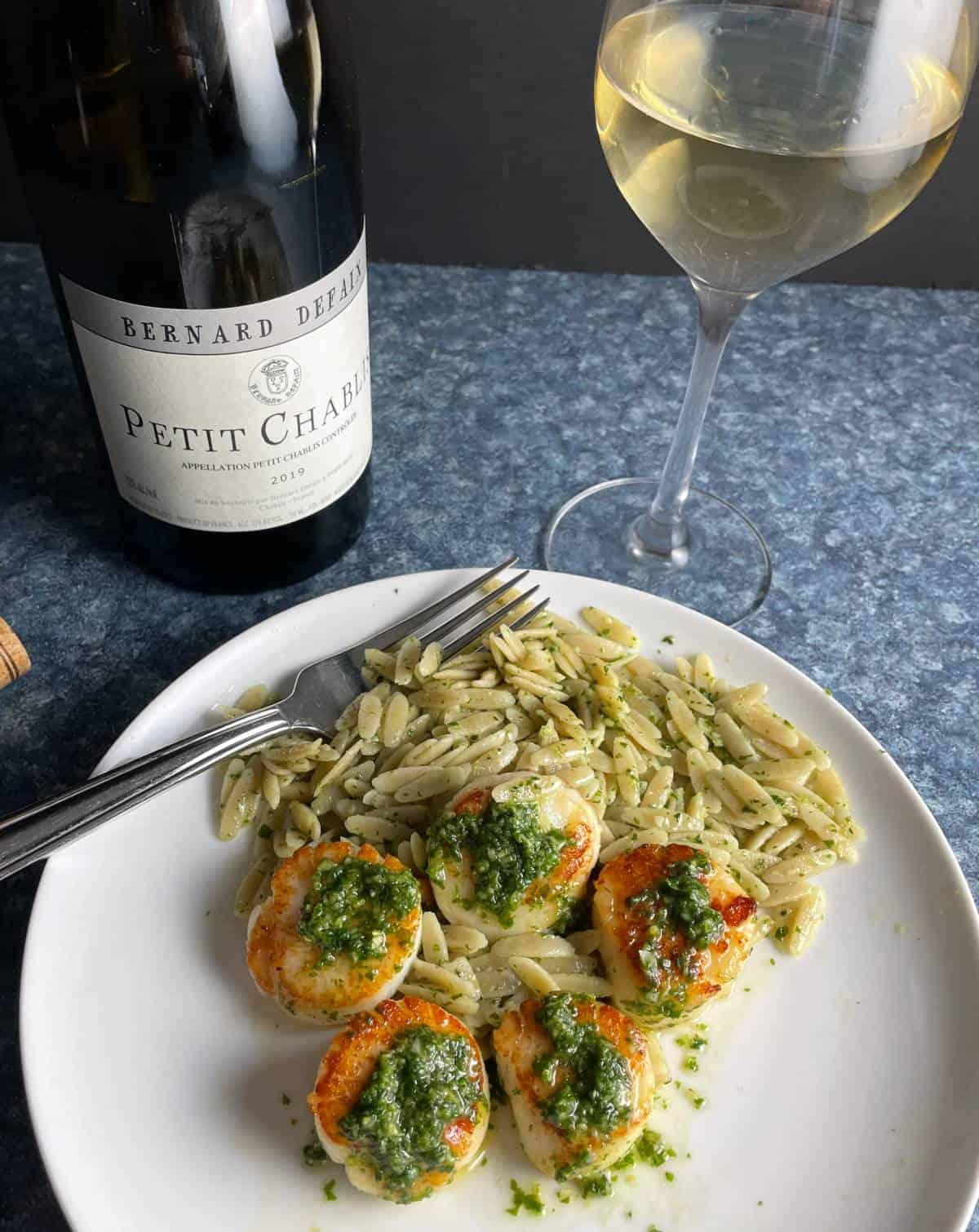 scallops served topped with pesto, and a bottle of Chablis white wine.