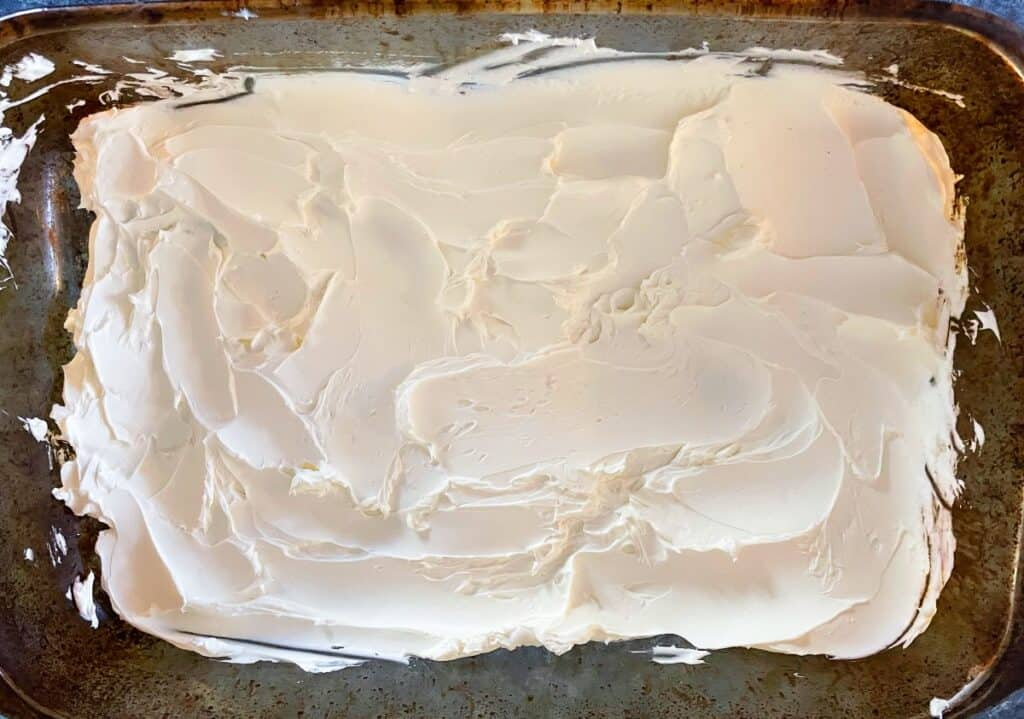 cream cheese spread out in the bottom of a baking dish.