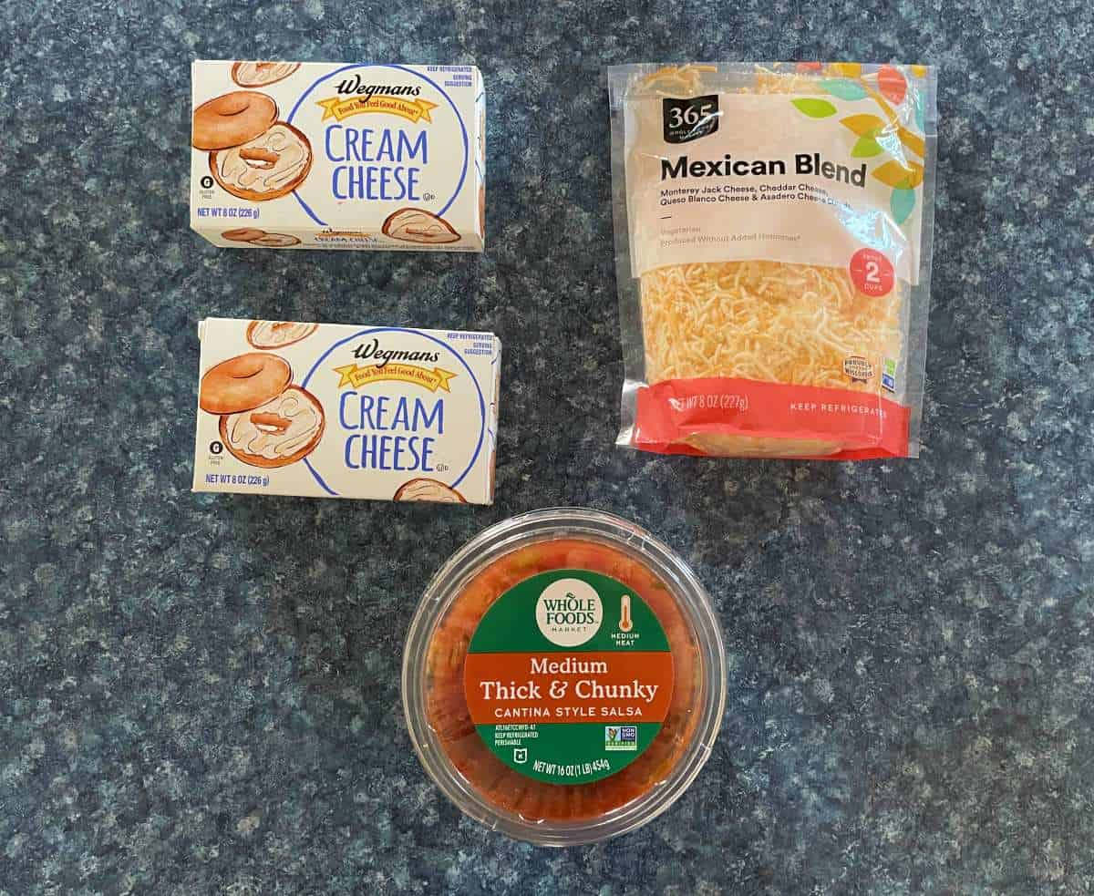 Ingredients for Mexican dip arranged on counter -- salsa, cream cheese and shredded cheese.