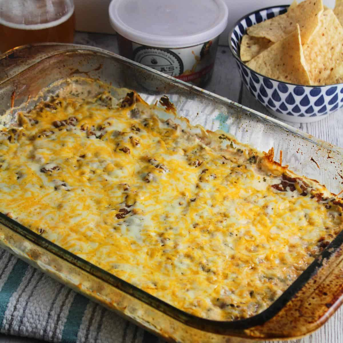 Easy Mexican Dip in a baking dish, with tortilla chips in the background.