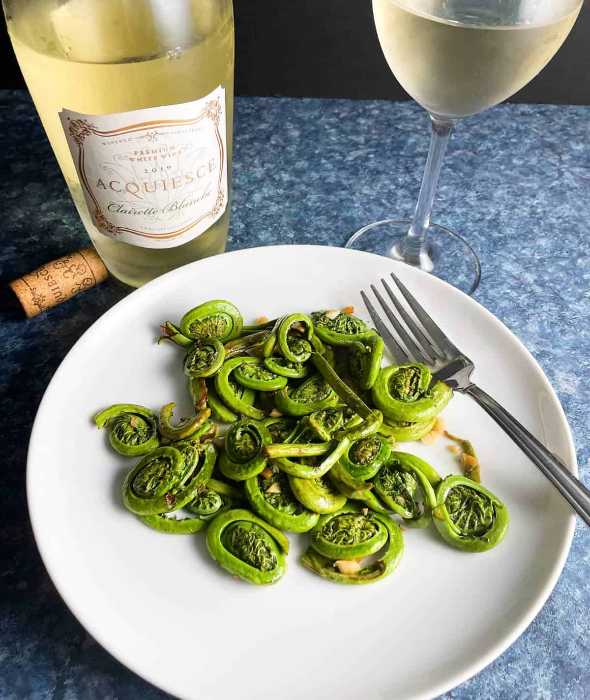 fiddlehead ferns served on a white plate along with a bottle and glass of whit wine.