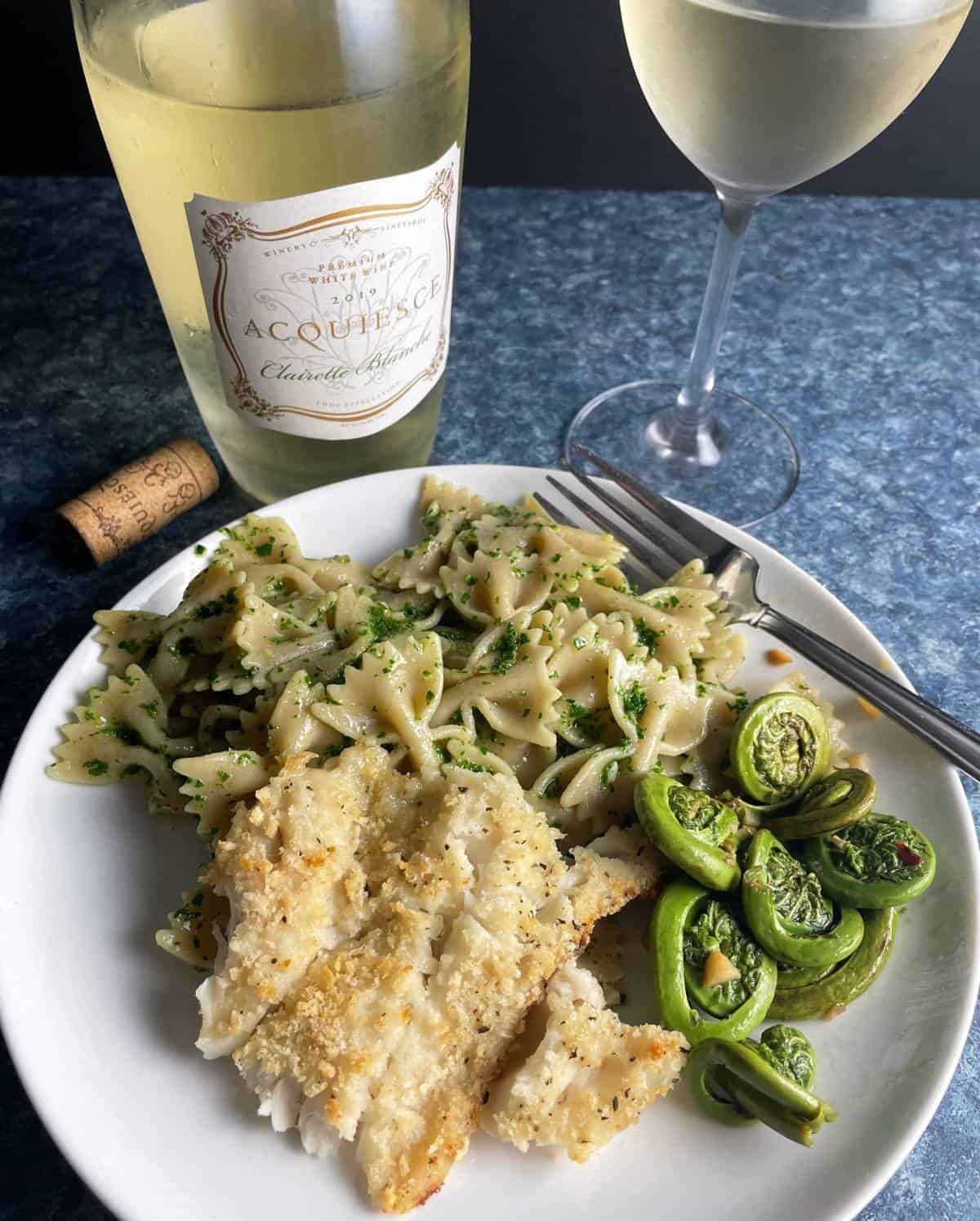 white plate with baked haddock, fiddlehead ferns and pesto pasta. With a white wine in the background.