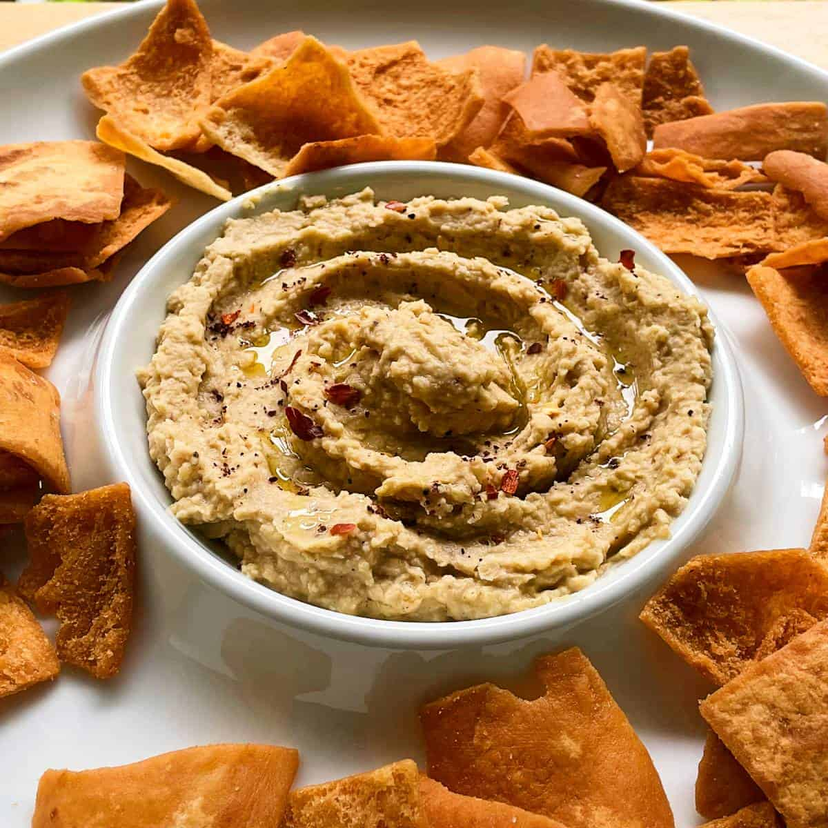 sesame free hummus in a white serving bowl with pita chips on the side.