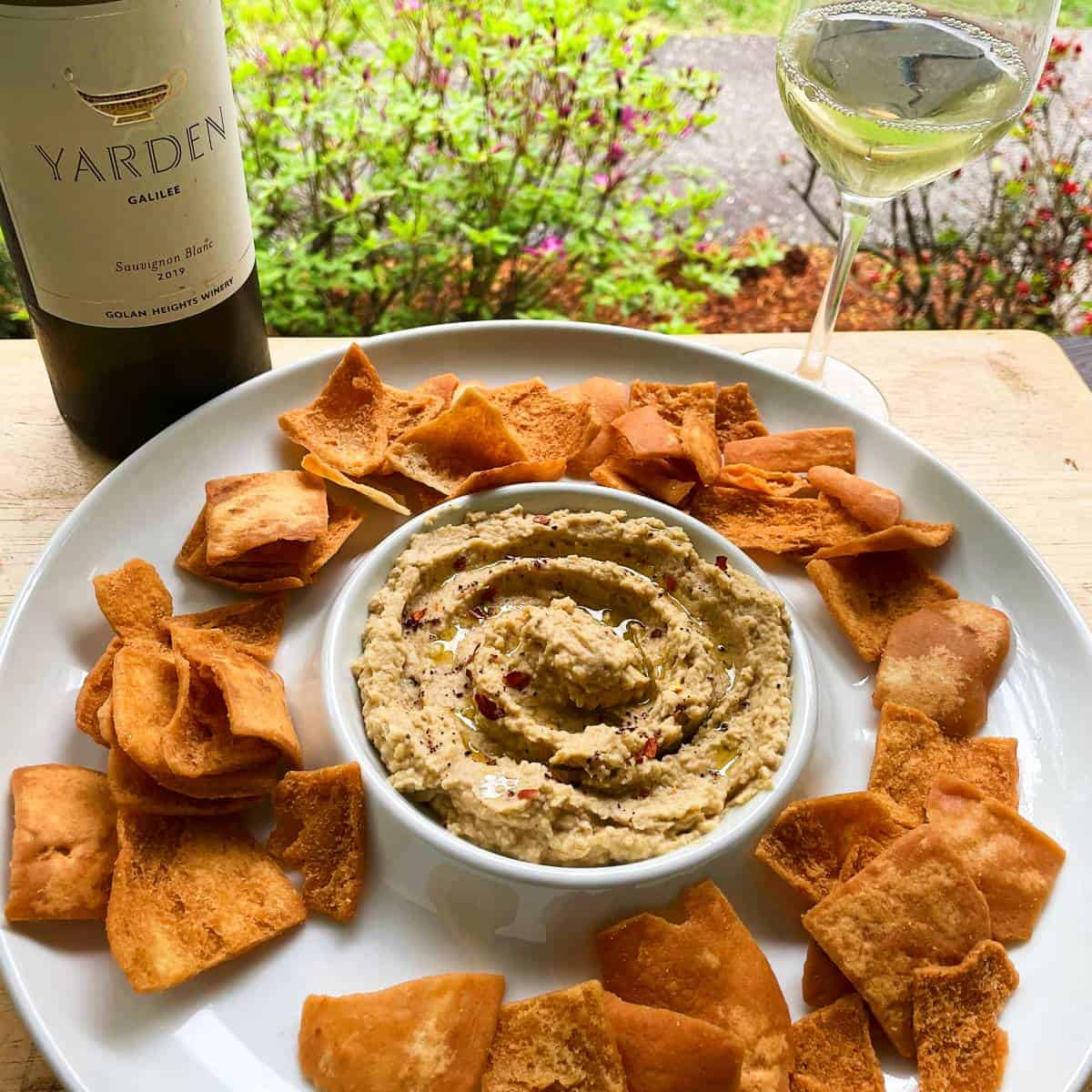 hummus in a white serving dish along with pita chips and Yarden Sauvignon Blanc wine.