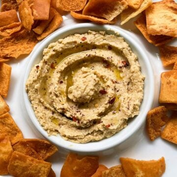 hummus in a white serving dish served with pita chips.