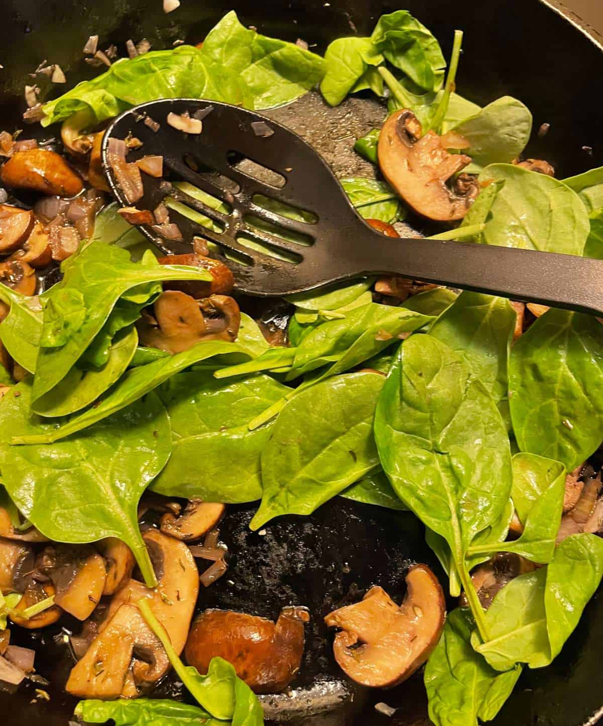 adding spinach to a skillet with mushrooms.