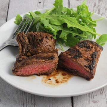 grilled steak tips on a white platter with a side of arugula greens.