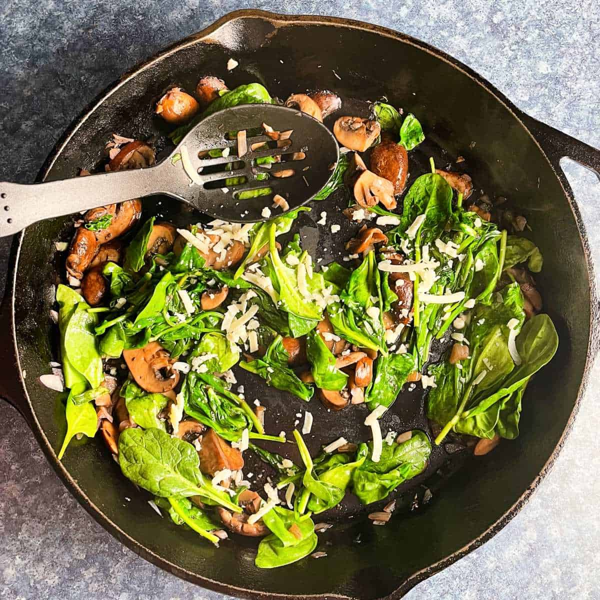 sauteed spinach and mushrooms in a large black skillet.