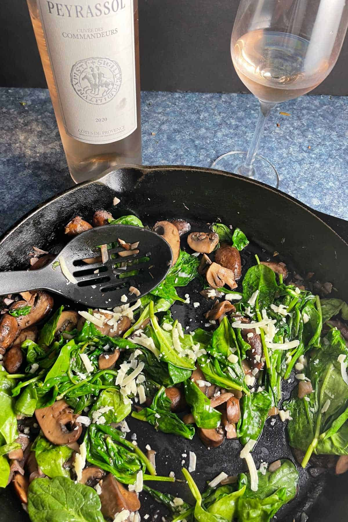 sautéed spinach and mushrooms in a skillet served with a rosé wine.