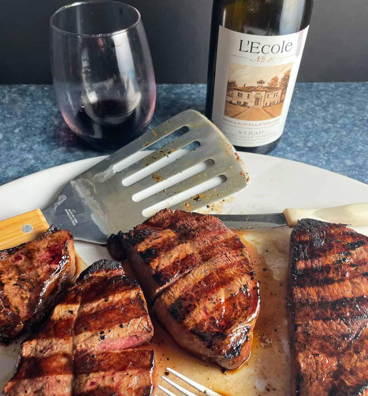 grilled steak tips on a white platter served with a Syrah red wine from L'Ecole No. 41.