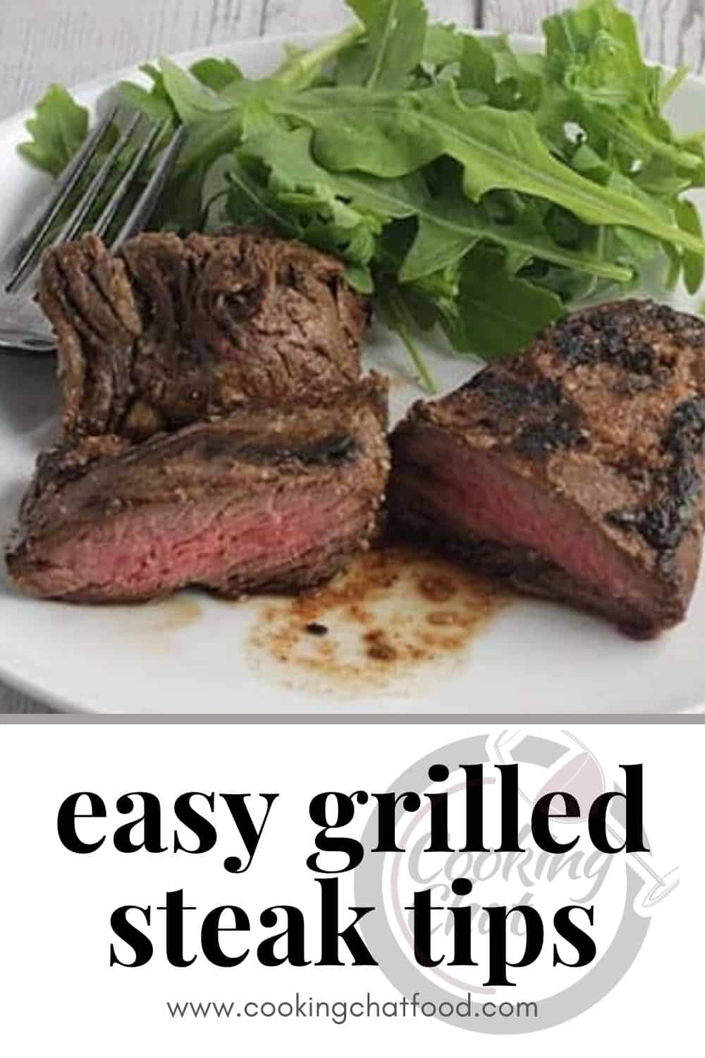 grilled steak tips served on a white plate with a side of greens.