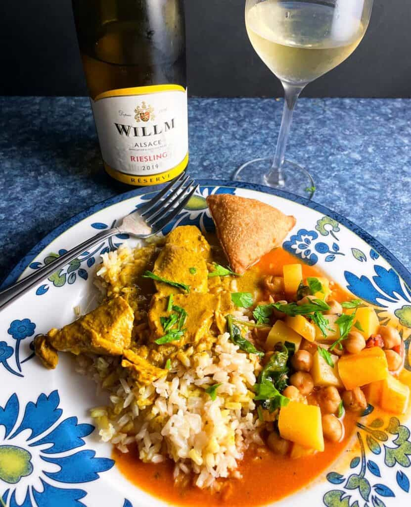 butternut squash chickpea curry plated with butter chicken and rice. Served with a Riesling white wine in the background.