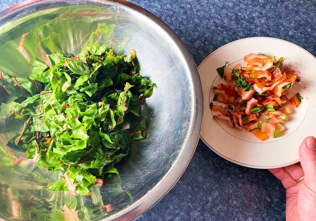 chopped chard leaves in a silver bowl with a plate of chopped chard stems alongside the bowl.