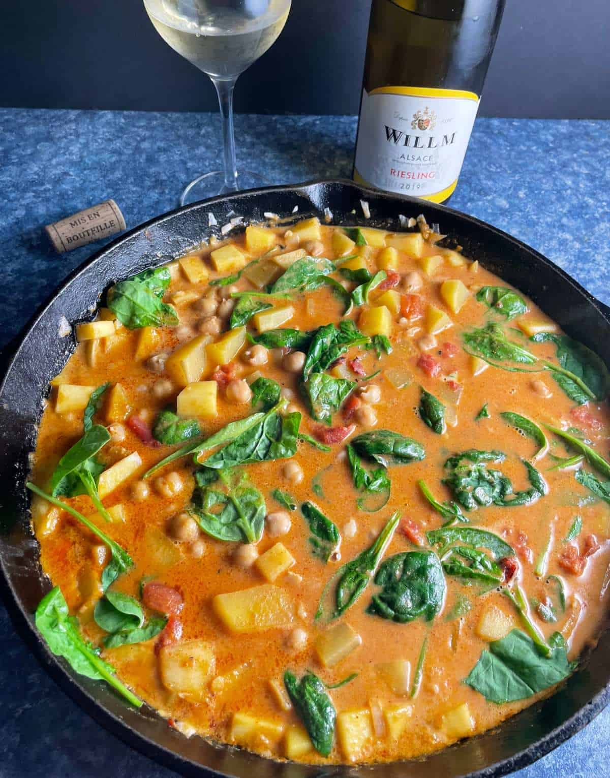 butternut squash chickpea curry in a large black skillet served with a Riesling white wine.