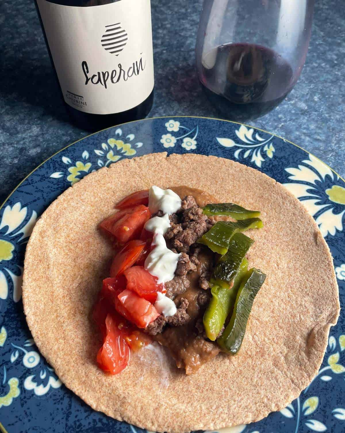 beef and bean tacos with peppers, sour cream and tomatoes, served on a plate with flowers on the edge. Red wine in the background.