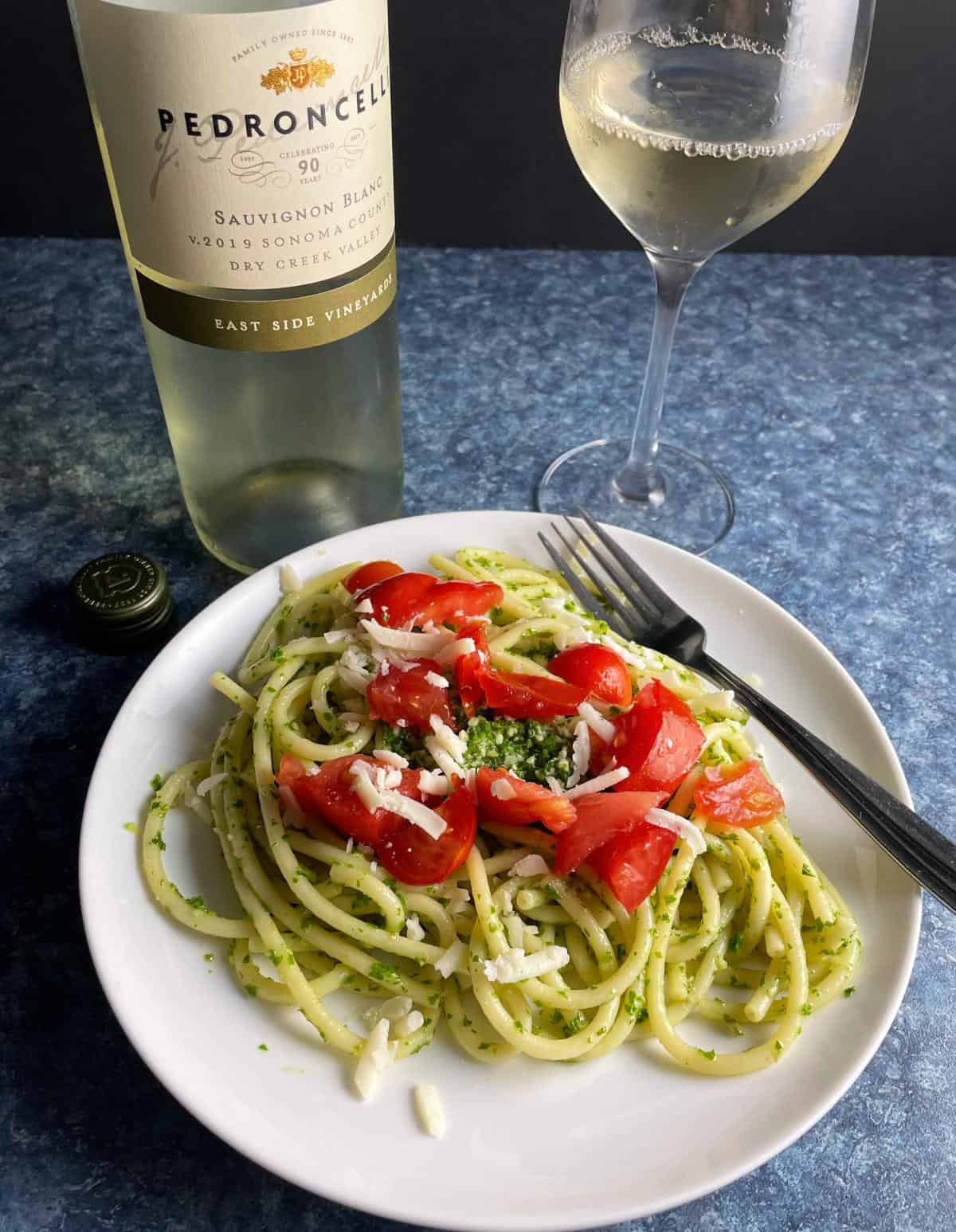 bucatini tossed with kale pesto and topped with fresh tomatoes. Served with a Sauvignon Blanc white wine.