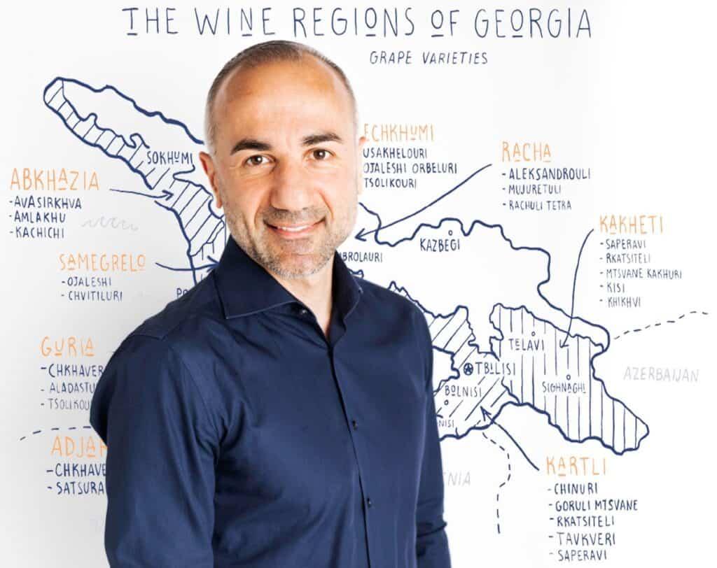 photo of Lasha Tsatava in front of a wine map of Georgia.