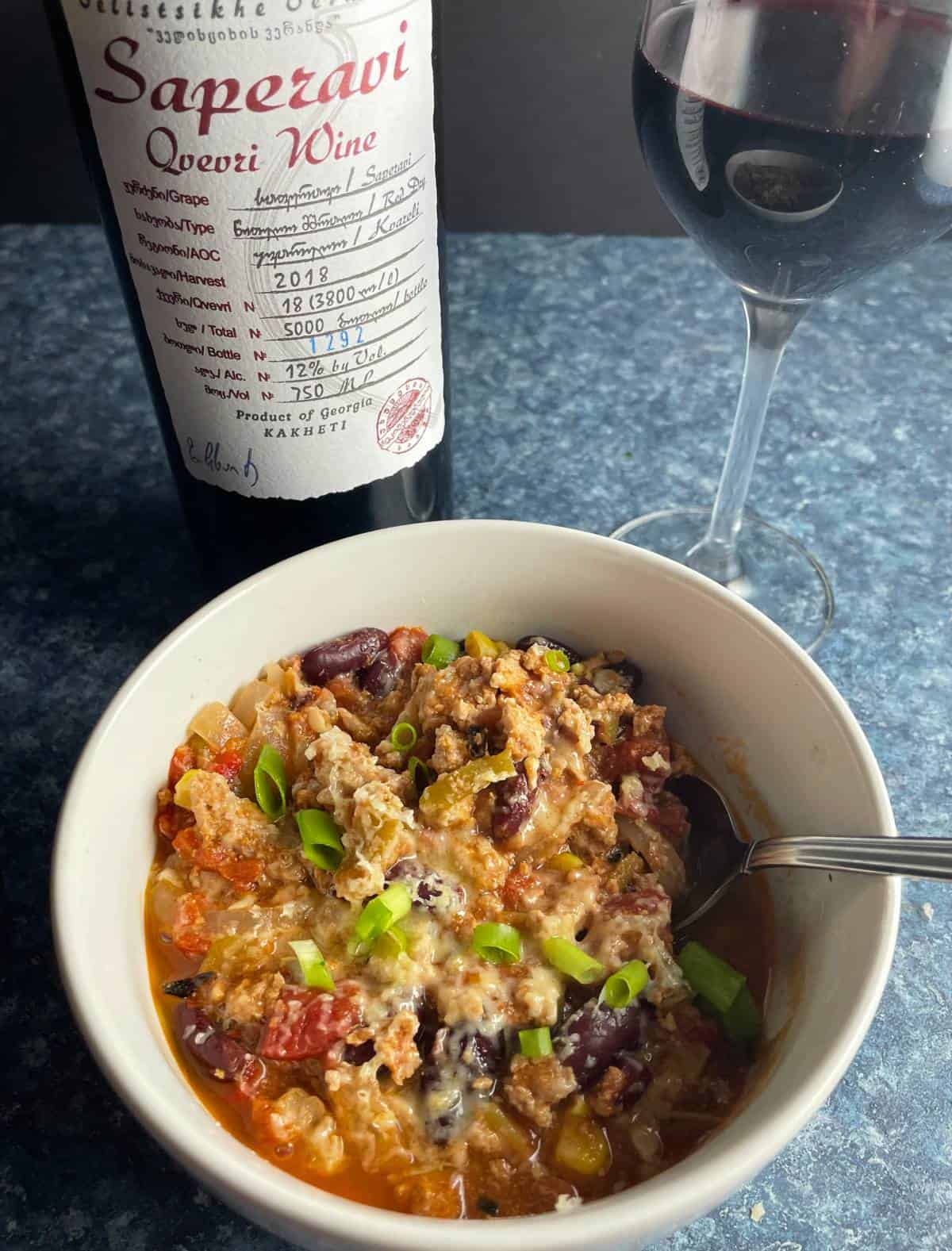 white bowl of turkey chili made with Hatch chiles with red wine in background.
