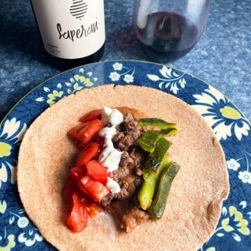 beef and bean tacos with peppers and tomatoes, served with a red wine.
