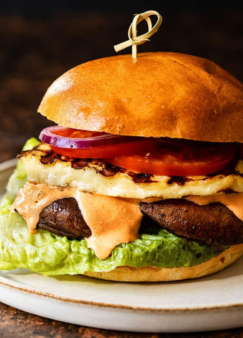 photo of a grilled halloumi burger topped with cheese and tomatoes, served on a bun.