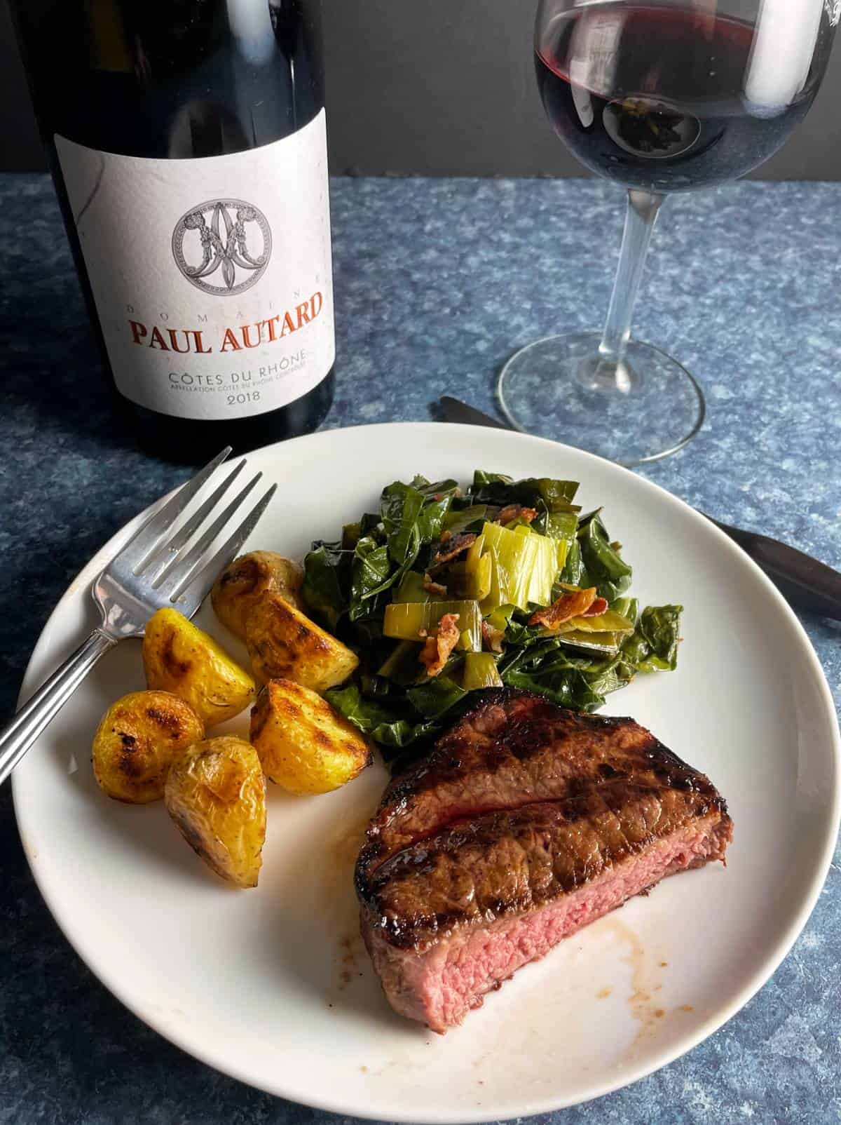 plate with grilled steak tips, collard greens and small potatoes. served with a red Cotes du Rhone wine.